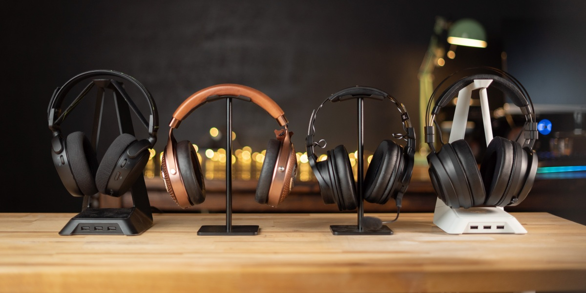 Four headphone stands with headsets on them