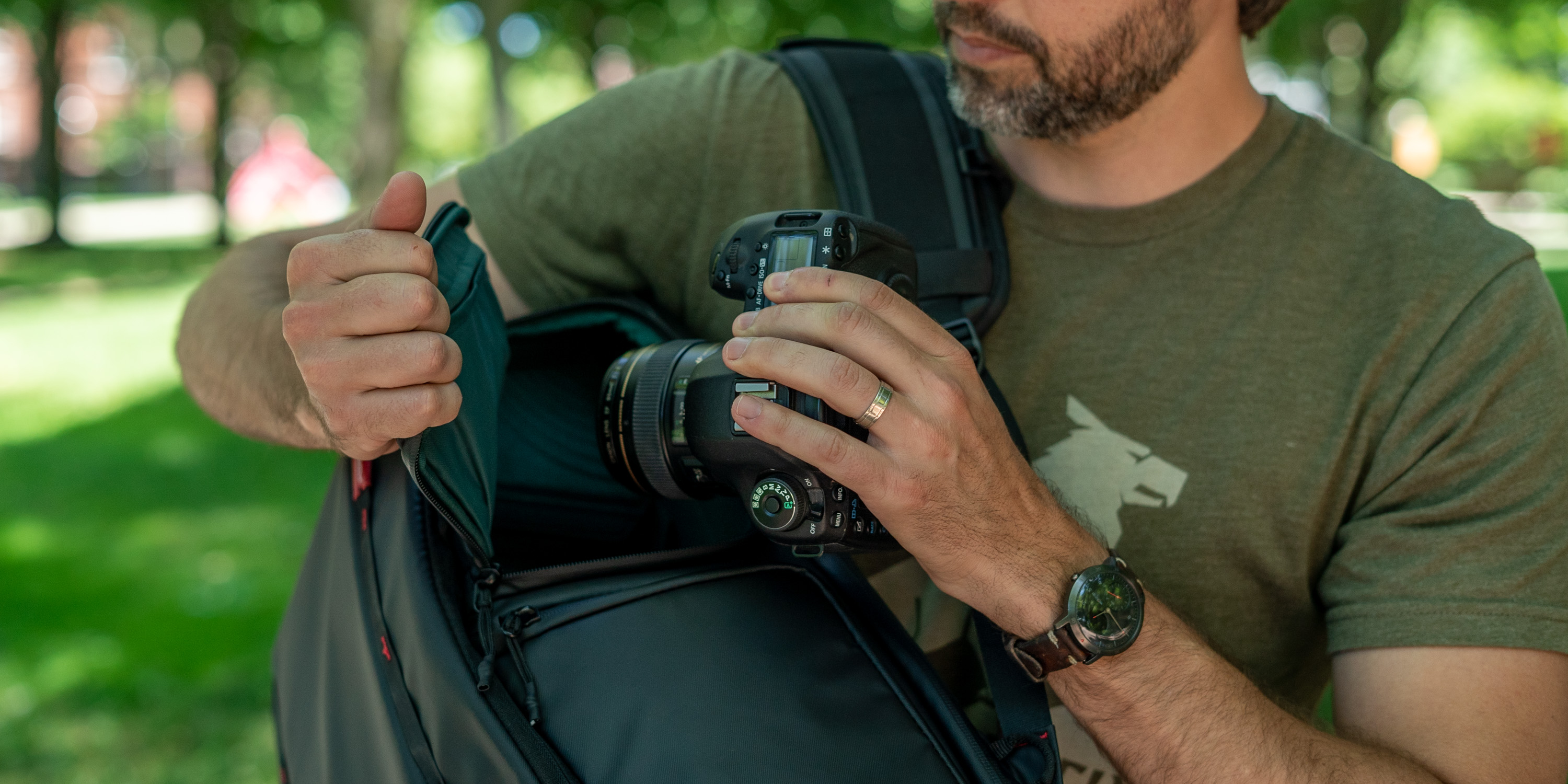 Pulling a DSLR out of the side pocket of the OneMo camera bag