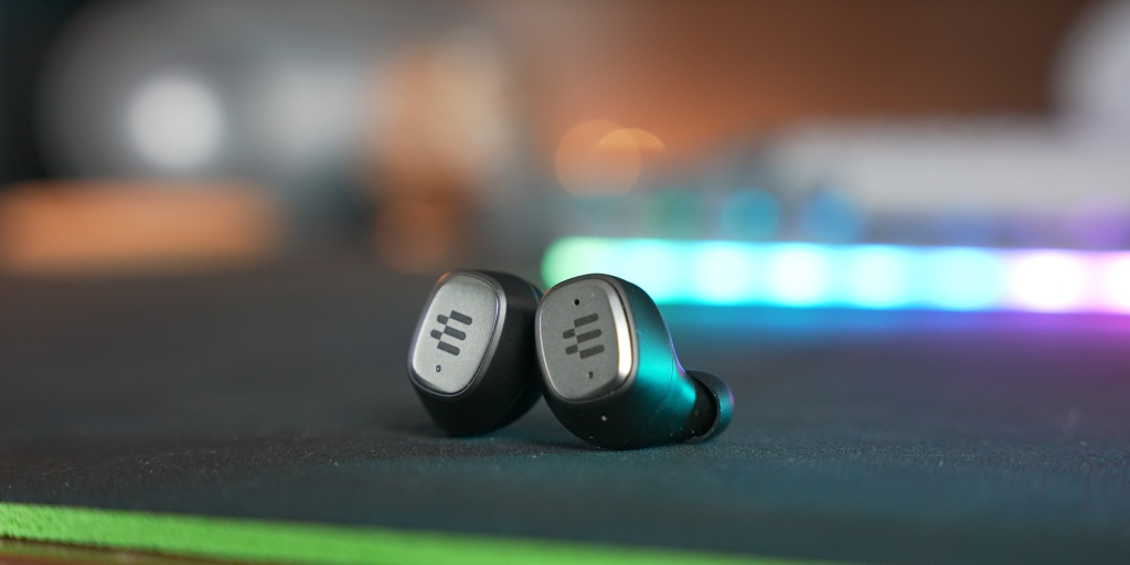 The earbuds have a simple design with a single tactile button on the left earbud.