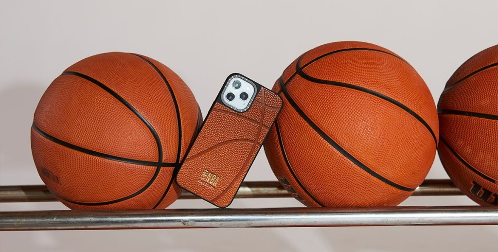 CASETiFY's leather NBA basketball case balanced next to a few basketballs on a rack.