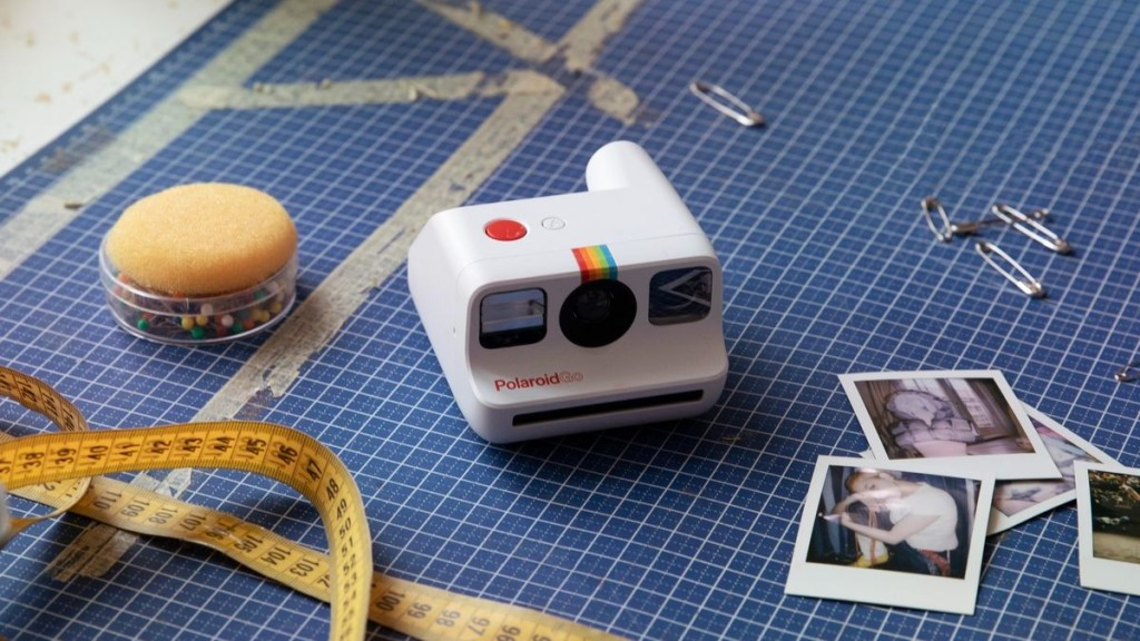 Polaroid Go camera sitting diminutively on a cutting mat, next to scattered sewing supplies and Polaroid Go pictures.