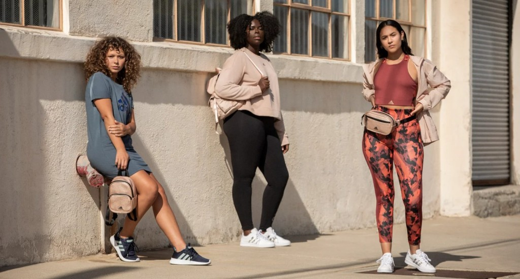 Three women on a city sidewalk sporting the adidas x Zoe Saldana activewear collection.