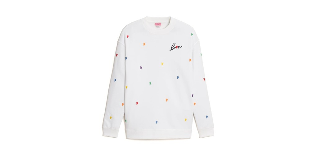 Kate Spade S21 Pride Collection white sweater dotted with small, multicolored embroidered hearts, and the word love with a red heart for a 'v' on the left breast