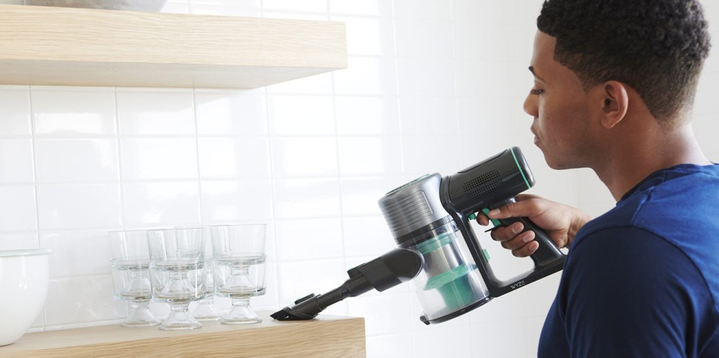 wyze cordless vacuum being used to clean a wood kitchen shelf